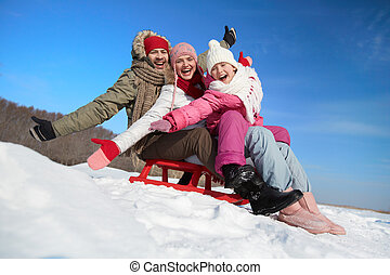 Family on sledge - Happy couple and their daughter sitting...