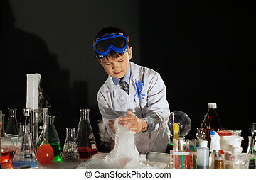 Image of little scientist watching experiment in studio