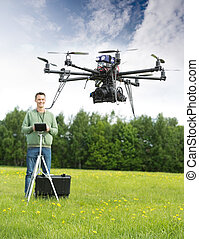 Man Flying UAV Helicopter in Park - Young man with remote...