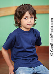 Cute Little Boy Sitting In Classroom