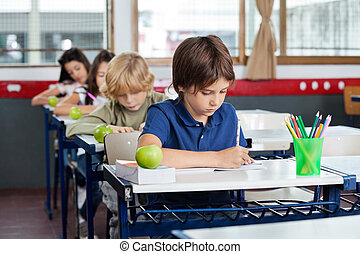 Schoolchildren Writing In Books At Desk - Elementary...