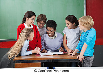 Female Teacher Teaching Schoolchildren At Desk - Young...