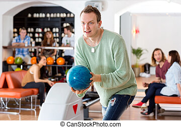 Man Playing in Bowling Alley At Club