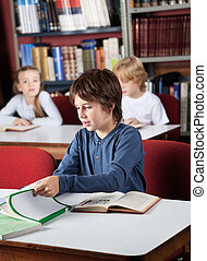 Schoolboy Studying In Library - Little schoolboy studying at...