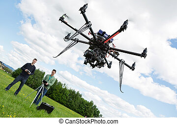 Technicians Operating UAV Helicopter in Park - UAV...