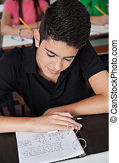 Teenage Schoolboy Reading Paper In Binder