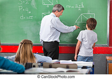 Teacher Assisting Schoolboy While Solving Mathematics -...