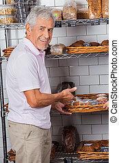 Senior Man Showing Muffins In Supermarket