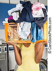 Woman Carrying Basket Of Dirty Clothes In Front Of Her Face