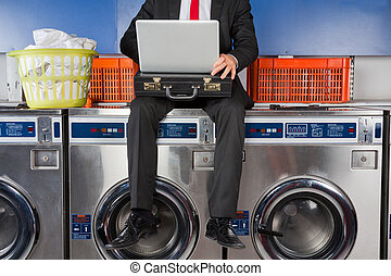 Businessman Using Laptop While Sitting On Washing Machine
