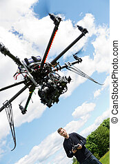 Male Engineer Flying UAV Helicopter - Low angle view of male...