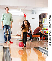 Happy Young Woman Bowling in Club - Happy young woman...