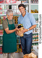 Customer With Salesman Putting Vegetable In Paper Bag