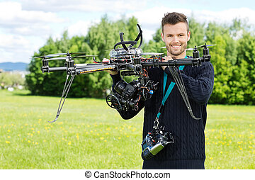 Technician Holding UAV Octocopter in Park - Portrait of...
