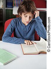 Schoolboy Reading Book At Table - Little schoolboy reading...
