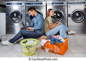 Couple Using Laptop And Earphones At Laundry - Man using...