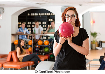 Young Woman Bowling in Club - Portrait of young woman...