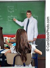 menina, sentando, em, escrivaninha, com, professor,...