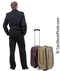 back view of adult man in black suit  traveling with suitcas .   Businessman looks ahead.  Isolated over white background. Rear view people collection. backside view of person.