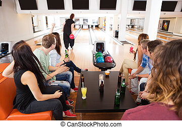 Friends Looking At Woman Bowling in Club - Group of young...