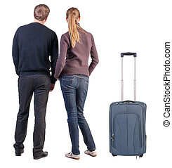 Back view of young couple traveling with suitcas . beautiful...