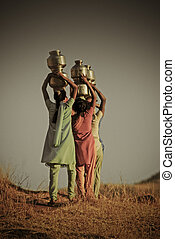Young women Carrying water from the local well, Maharashtra,...