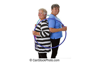 Senior lady doing gymnastic with hula hoop - isolated on...