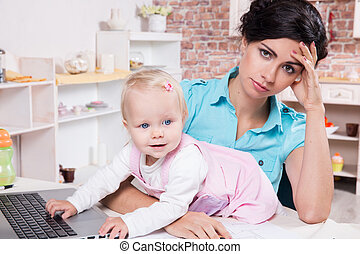 business woman with laptop and her baby girl - Young...