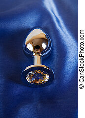 Metal butt plug on blue satin - Metal sex toy butt plug on...