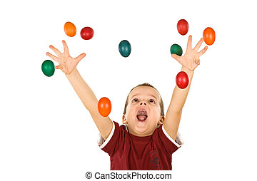 Happy boy reaching for the falling easter eggs
