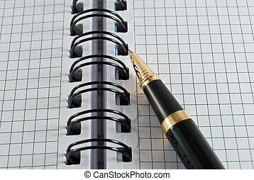 pen and notebook - a pen and notebook is on a spiral
