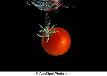 Fresh tomato dropped into water, isolated on dark background...