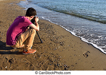 young photographer taking pictures on the beach