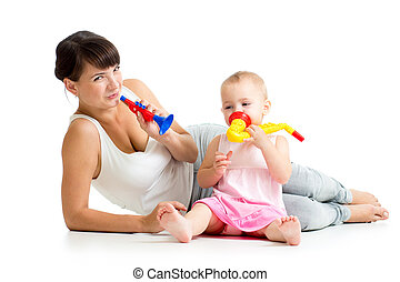 Mother and baby girl having fun with musical toys. Isolated on white background