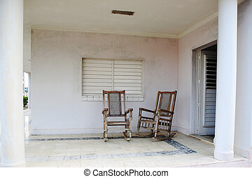 Two old wooden chairs on the porch in Cuba
