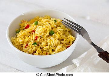 Curryreis in einer Schale auf weiem Holztisch