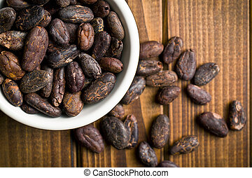 cocoa beans in bowl on wooden table