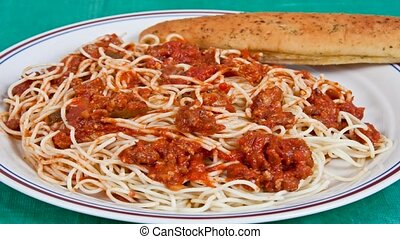Spaghetti with meat sauce on a plate with bread