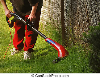 Lawn Care Edging - Weed wacker used to trim fence line on...