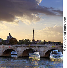 Paris sunset skyline with bridge over Seine river and Eiffel tower in France.