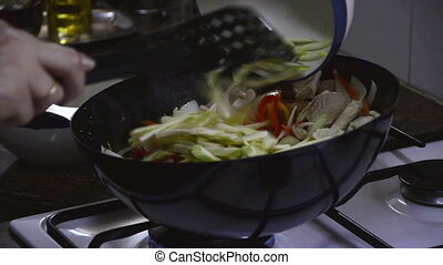 Add zucchini to frying chicken - Adding zucchini to frying...