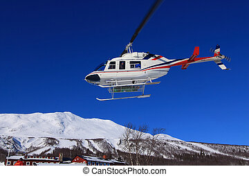 Heli skiing headed for the mountin peak. - Skiers air bound,...