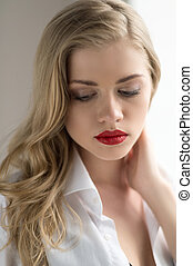 Thoughtful blond. Beautiful blond hair woman holding her hand in hair and looking down