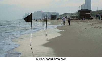 Dreary beach morning - Black flags on the beach, low...