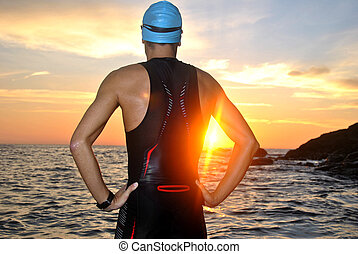 young athlete triathlon in front of a sunrise over the sea