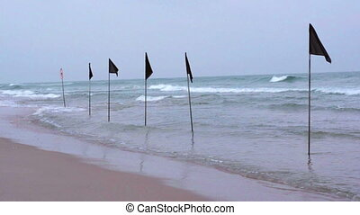 Black flags on the beach