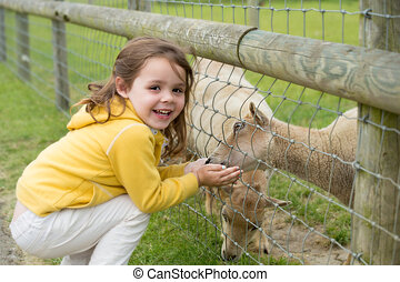 Child feeding a goat - little girl on a farm feeding a goat