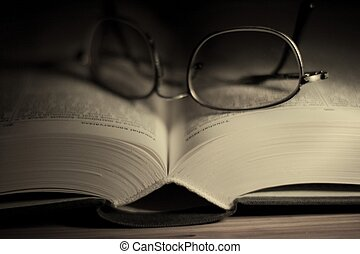 Book - Open book with glasses in dark environment