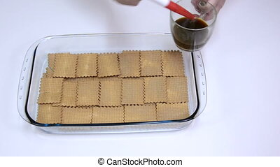 Brushing biscuits with black coffee - Confectioner brushing...