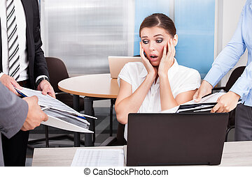 Shocked Businesswoman Looking At Folders Being Surrounded By...